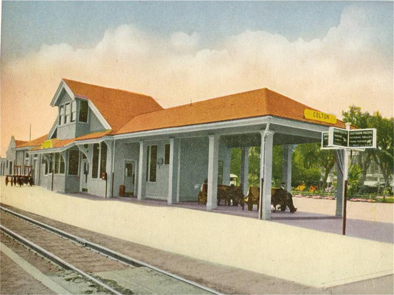 An older image of a train depot with patrons waiting on park benches